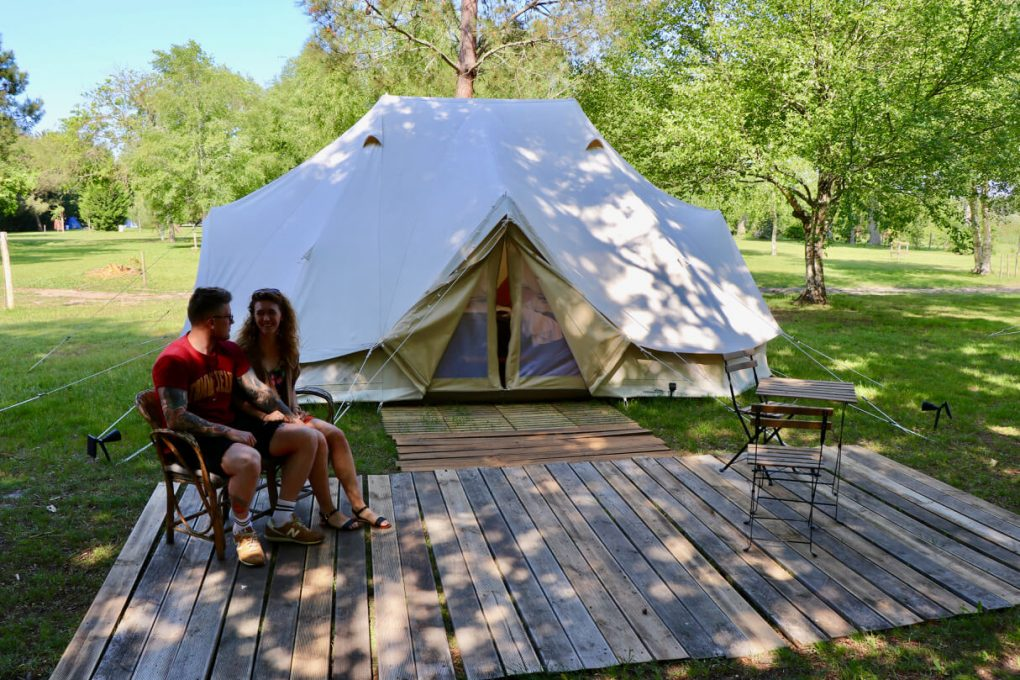 Abbi and Isaac are sat on a bench outside a large white bell tent where they are glamping in Bordeaux, France.