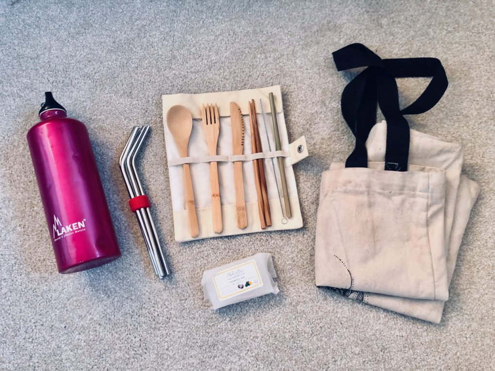 A flat-lay of plastic-free travel gear: a reusable water bottle, metal straws, bamboo cutlery, a reusable tote bag and a shampoo bar.