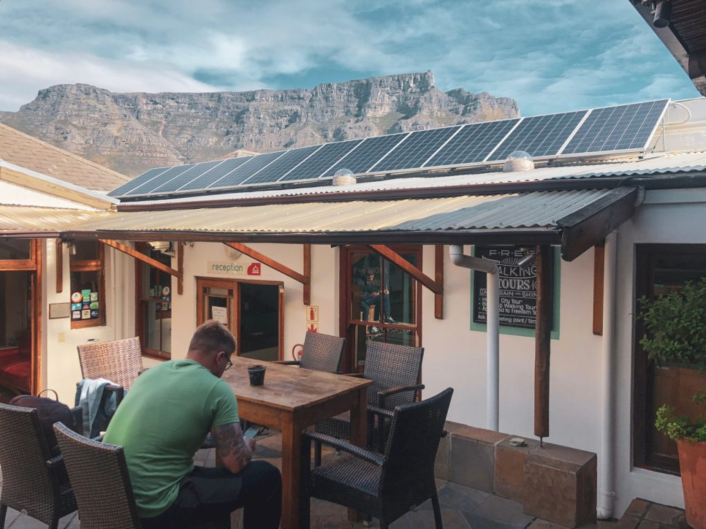 A hostel in South Africa has solar panels on the roof. Table Mountain is visible in the background, against a blue sky.