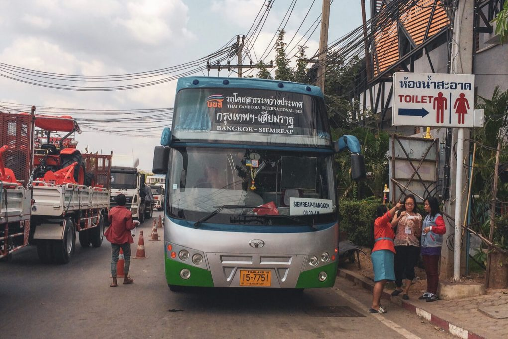 A Thai Bus stopped beside a Toilet sign, the bus is from Bangkok to Siem Reap.
