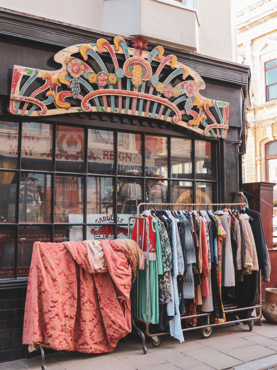 A vintage shopfront with a rail of vibrantly coloured clothes outside - One Day in Margate