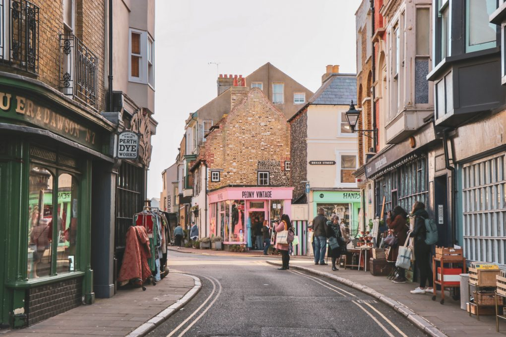A quirky street in Margate, with vintage stores on each side of the narrow road. The buildings are a clash of brick, wood, chimneys, rendered cream fronts, and brightly coloured signs. The railings and streetlights and windows all clash too. A few people are taking photos.