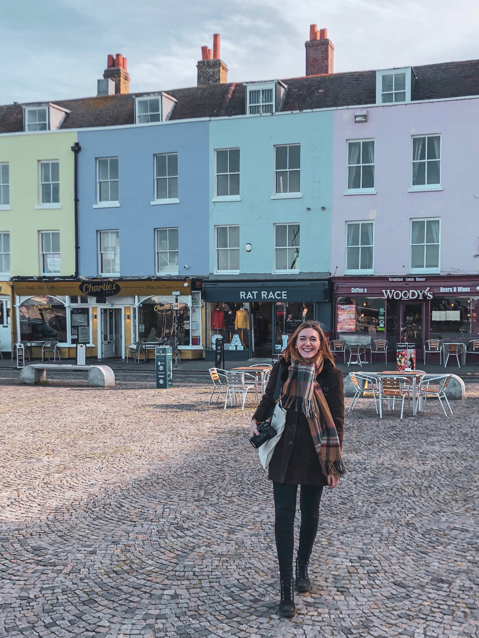 Abbi is standing in front of pastel-coloured buildings on Margate's seafront - One Day in Margate
